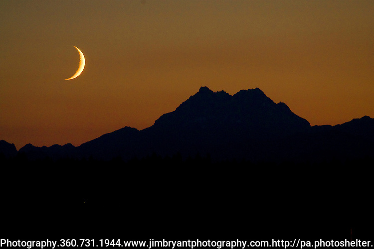 A waxing crescent moon sets over the Olympic Mountains  on Friday, July 24, 2009.In  the northern hemisphere, if the left side of the Moon is dark then the light part is growing, and the Moon is referred to as waxing (moving towards a full moon). If the right side of the Moon is dark then the light part is shrinking, and the Moon is referred to as waning (moving towards a new moon). &copy;2009. All Rights Reserved. Jim Bryant Photo