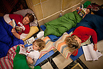 From left, high school teacher Beth Wojciuk, eight-year-old Abby Glassford, high school teacher Jen Glassford, and eight-year-old Charlie Glassford prepare to spend the night while protesting a bill to eliminate collective bargaining at the State Capitol in Madison, Wisconsin, February 24, 2011.