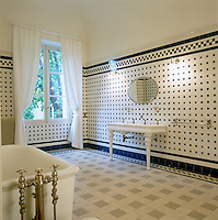 Stunning black and white tiles are laid in a geometric pattern in this gloriously old-fashioned bathroom