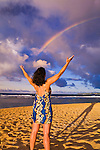 Rainbow over woman raising arms on Tunnels Beach at sunset, Island of Kauai, Hawaii USA