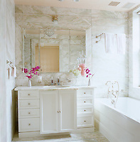 The master bathroom is a luxurious creation in peach onyx which lines the walls and floor