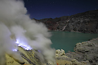 Kawah Ijen Volcano, Java, Indonesia showing acidic crater lake and blue burning sulfur flames and gas.