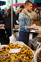 London, UK. 25.10.2014. Young man on a stall selling Portuguese custard tarts at Borough Market, Southwark. Photograph © Jane Hobson.