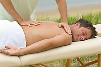Man enjoying getting an outdoor massage my another man
