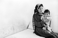 An ethnic Hazara woman with her child in the hospital in Jaghori, Afghanistan on Thursday,  June 20, 2002. She is one of thousands of Hazara refugees who have returned to Afghanistan from Iran to try to rebuild their lives. More than six million people fled Afghanistan during the years of conflict following the Soviet invasion in 1979.