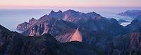Evening light over mountain landscape from rocky summit of Hermannsdalstinden, Moskenesoy, Lofoten Islands, Norway