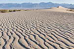 Death Valley National Park, California; ripples in the sand in the Mesquite Flat Sand Dunes in early morning sun and shadows, with the Amargosa mountain range in the background