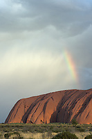 A rainbow appears over Uluru/Ayers Rock during a passing rain shower