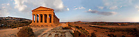 Panoramic view of the Temple of Concord, 5th century BC, and surrounding landscape, Agrigento, Sicily, Italy,  pictured on September 11, 2009, in the warm evening light. Well preserved owing to its 6th century AD conversion to a church, the Temple of Concord is a typical example of optical correction whose tapering columns create the illusion of a perfectly aligned building. Its frieze consists of alternating triglyphs and metopes, and the pediment is undecorated. The Valley of the Temples is a UNESCO World Heritage Site. Picture by Manuel Cohen.
