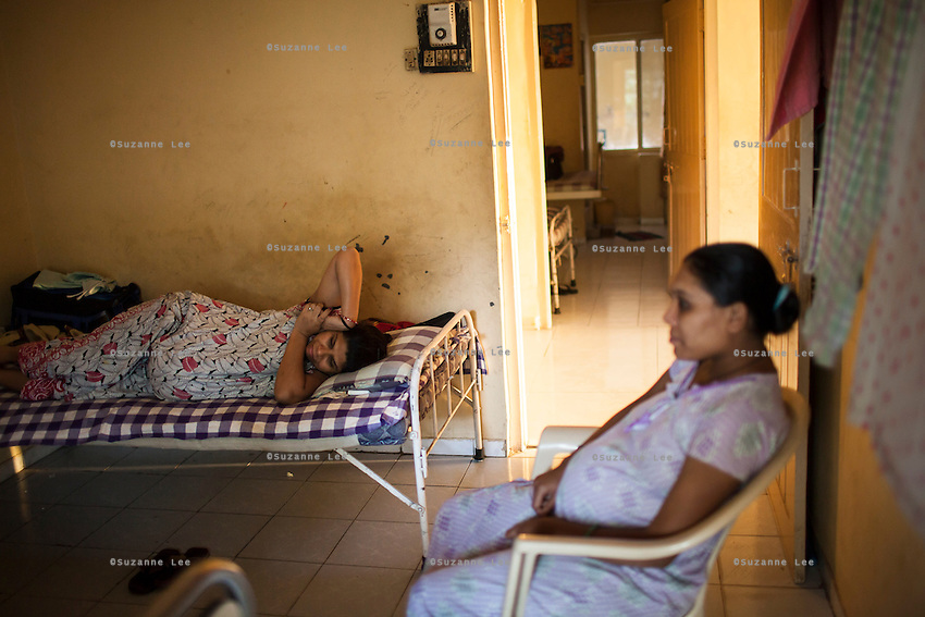 9 months pregnant, Leela Mekwan (left), 34, rests while chatting with other surrogates as they while their time away in the surrogates hostel on the 3rd floor of Dr. Nayana Patel's Akanksha IVF and surrogacy center in Anand, Gujarat, India on 10th December 2012. Photo by Suzanne Lee / Marie-Claire France