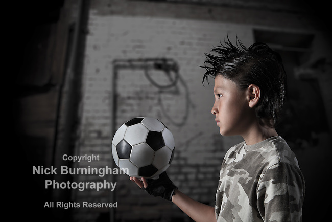 A young boy plays street soccer against a graffiti covered wall - with dramatic lighting and subdued colors - EXCLUSIVELY AVAILABLE HERE and ALAMY