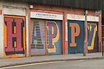 Middlesex Street East End London E1. Alphabet Street project &quot;HAPPY&quot; on shop shutters work by street artist Ben Eine (real name Ben Flynn).