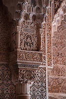 Polychrome mocarabe work above a pillar, and intricately carved stucco walls with floral decoration, in the Court of the Lions, built 1362 in the second reign of Muhammad V, in the Nasrid dynasty Palace of the Lions, Alhambra Palace, Granada, Andalusia, Southern Spain. The Alhambra was begun in the 11th century as a castle, and in the 13th and 14th centuries served as the royal palace of the Nasrid sultans. The huge complex contains the Alcazaba, Nasrid palaces, gardens and Generalife. Picture by Manuel Cohen