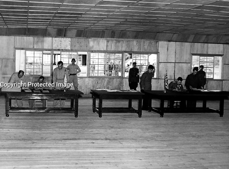 Gen. W. K. Harrison, Jr., signs armistice ending 3-year Korean conflict.  Gen. Harrison, left table, and North Korean Gen. Nam II, right table, sign documents.  July 23, 1953.  F. Kazukaitis. (Navy)<br /> NARA FILE #:  080-G-625728<br /> WAR &amp; CONFLICT BOOK #:  1517