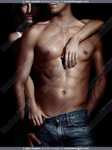Sexy couple photo in dark dramatic light of a young woman standing behind a man with muscular bare torso and pulling his jeans down. Isolated on black background.
