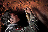 A KIA cobra soldier enters into an anti-shelling shelter as he overhauls the stocks of bombs used during the fighting in Maiya Jang front line, the second largest city under control of the Kachin Independence Army. The KIA positions around the city have been attacked by shelling and heavy artillery during months. Fierce clashes have taken place since the ceasefire was broken out by the Burmese army last June 2011. During months the fighting were spread out along the Kachin State leaving more than 40,000 displaced persons and refugees (a conservative estimating) in accord with the humanitarian aid groups.