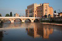 The Seher-Cehaja Bridge, a 16th century Ottoman bridge crossing the Miljacka river, and behind, the National and University Library of Bosnia and Herzegovina, the national library, designed in 1891 by the Czech architect Karel Parik as the City Hall, and reopened as a library in 2014, Sarajevo, Bosnia and Herzegovina. This building, on the banks of the Miljacka river, is from the Austro-Hungarian period of the city. The building and many of its documents were damaged in 1992 during the Siege of Sarajevo in the Yugoslav War. Picture by Manuel Cohen