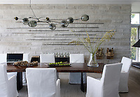 The dining area in the family room combines the materials of timber, linen and a textural wall of concrete. The variations add character and a tonal richness to the room. A collection of ceremonial spears are displayed on the wall and a branching bubble light fixture hangs above the teak slab table.