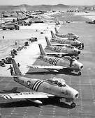 F-86 airplanes wait on a flight line June 1951. The F-86, the United States Air Force's first swept-wing jet fighter, made its initial flight October 1, 1947. The first production model flew May 20, 1948. On September 15, 1948 an F-86A set a new world speed record of 670.9 miles per hour. Originally designed as a high-altitude day-fighter, it was subsequently redesigned into an all-weather interceptor (F-86D) and a fighter-bomber (F-86H)..Credit: U.S. Air Force via CNP
