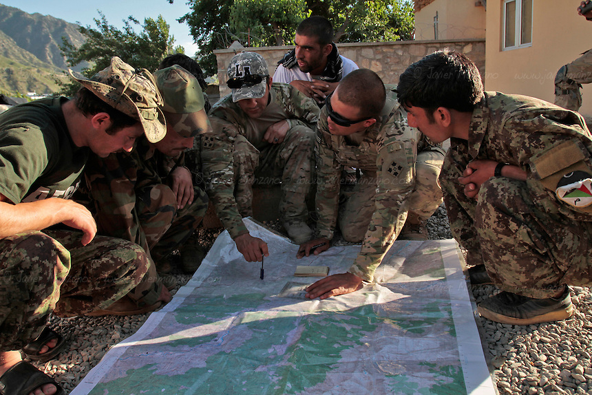 Members of the Afghan National Army are taught how to read topographic maps by a United States Army soldier in Kunar Province. The vast majority of Afghan soldiers cannot read topographic maps - added to the challenges of forming a National Army is the overall national illiteracy rate of 17% - this means that in many cases, Afghan National Army soldiers will not be able to call in air strikes from NATO planes because they cannot give accurate grids to their NATO counterparts. The American forces are working really hard to achieve an acceptable level of operational independence post 2014. Many challenges still remain. ...(PHOTO: Javier Manzano). ..