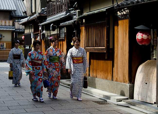 Japanese girls dress in kimonos and walk though the ancient Gion district in Kyoto, Japan.