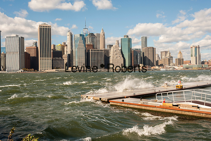 The windy, choppy waters of the East River break against a breakwater in Brooklyn Bridge Park in New York on Sunday, October 23, 2016. Wind gusts reached 55 mph with the city issuing a wind advisory. Monday is expected to be warmer with less wind. (©Richard B. Levine)