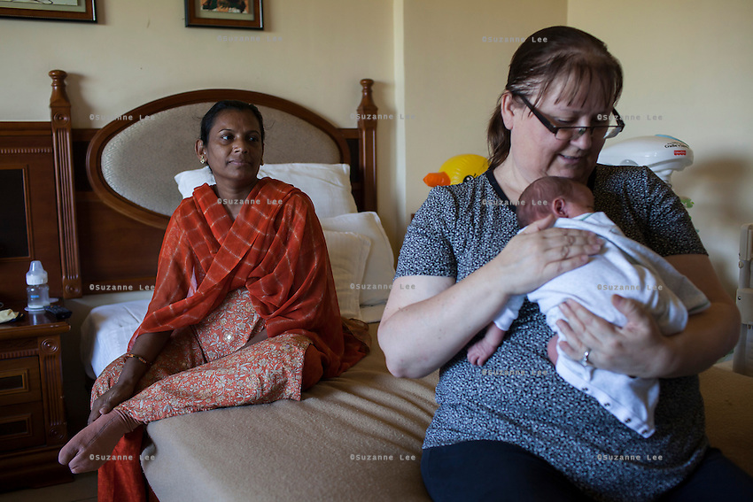 Barbara, from Canada, carries her baby after her surrogate, Idan, has breastfed the baby in her hotel room near the Akanksha Clinic in Anand, Gujarat, India on 11th December 2012. Barbara, from Canada, had come to receive him at his birth from Idan, her surrogate, and is waiting for her husband to come and join her in Anand, while she continues to hire Idan to breastfeed her son so that he gets the best start in life. Idan's husband sends pumped breast milk to Barbara's hotel in the evenings when Idan cannot come personally. Photo by Suzanne Lee / Marie-Claire France