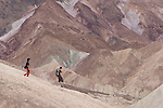 Two hikers descend into the hills of Zabrieskie point in Death Valley.