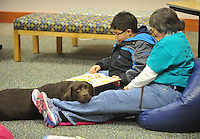 NWA Democrat-Gazette/Michael Woods --01/14/2015-- w @NWAMICHAELW... Eric Suarez reads a book with Denise Johnson, a volunteer with the Springdale Public Library and Wiggles, a therapy dog, during Wednesday evenings session of the Kibbles and Books program at the Springdale Public Library. Kibbles & Books is a literacy program designed to build confidence in young readers by reading out loud to therapy dogs giving the children a chance to practice their literacy skills in a stress-free and fun context.