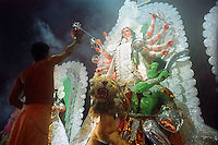 INDIA (West Bengal - Calcutta)  2006,A ritual of evening worship called 'ARATI' at a pandal on one of the days of Durga Puja Festival. Durga Puja Festival is the biggest festival among bengalies.  As Calcutta is the capital of West Bengal and cultural hub of  the bengali community Durga puja is held with the maximum pomp and vigour. Ritualistic worship, food, drink, new clothes, visiting friends and relatives places and merryment is a part of it. In this festival the hindus worship a ten handed godess riding on a lion armed wth all possible deadly ancient weapons along with her 4 children (Ganesha - God for sucess, Saraswati - Goddess for arts and education, Laxmi - Goddess of wealth and prosperity, Kartikeya - The god of manly hood and beauty). Durga is symbolised as the women power in Indian Mythology.  In Calcutta people from all the religions enjoy these four days of festival in the moth of October. Now the religious festival has become the biggest cultural extravagenza of Calcutta the cultural capital of India. Artistry and craftsmanship can be seen in different sizes and shapes in form of the idol, the interior decor and as well as the pandals erected on the streets, roads and  parks.- Arindam Mukherjee