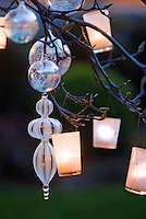 Detail of glass baubles and tealights hanging from a trees bare branches