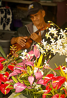 Flower vendor playing an ukelele at the Hilo Farmers Market