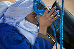 Moroccan man dressed with turban drinks water from a well in the Sahara desert.