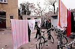 Courtyard of courthouse, at left, in Tsing Tao, China.  Laundry from the military units hangs on the lines and the defendant in a murder trial crouches in the distance by a garage door before the trial.