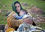 A refugee mother holds her child after landing on a beach near Molyvos, on the Greek island of Lesbos, on October 30, 2015. They crossed the Aegean Sea from Turkey in a small overcrowded boat, for which they paid Turkish traffickers huge sums. They were received in Greece by local and international volunteers, then proceeded on their way toward western Europe.
