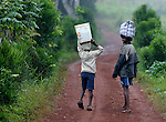 A girl carrying a package on her head looks back as she and a boy carrying water walk on a path through Mizak, a small village in the south of Haiti.
