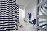 A small sitting room is concealed beneath the main hotel and shielded by blue and white striped curtains which blow gently in the breeze