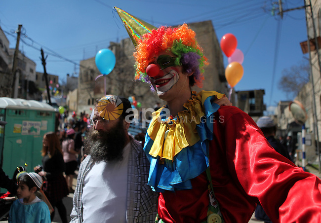 Israeli settlers dance with a clown during celebrations marking the Jewish holiday of Purim in the occupied West Bank city of Hebron March 5, 2015. Purim is a celebration of the Jews' salvation from genocide in ancient Persia, as recounted in the Book of Esther. Photo by Mamoun Wazwaz