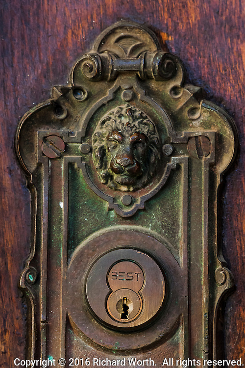 A door, an entrance, to the Meek Mansion, and that door's ornate handle, including a lion's head.