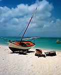 Yacht and small boats beached on the shore. Barbados, circa 1976.