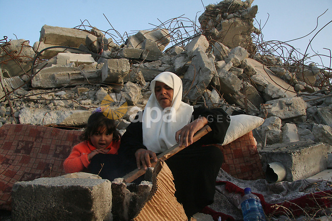 A Palestinian family sit on the rubble of their home destroyed during Israel's 22-day offensive in Jabalia in the northern Gaza Strip on  February 16, 2009. Israeli aircraft struck smuggling tunnels on Gaza's border with Egypt, after two rockets were fired from the Palestinian territory, witnesses said. The attacks came despite ceasefires declared on January 18 after a three-week Israeli offensive against the territory's Hamas rulers that killed 1,330 Palestinians  APAIMAGES PHOTO / Ashraf Amra
