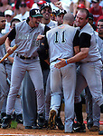 6/2/06 Lincoln, NE Manhattan University's John Fitzpatrick (No.11) is mobbed by his teammates at home plate after hitting a home run in the 2nd inning against the University of Nebraska at Haymarket Park in Lincoln Ne Friday afternoon.  Manhattan one 4-1.(Chris Machian/Prairie Pixel Group)