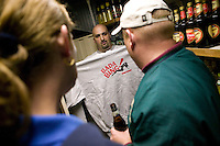12 March 2006 - Lodi, NJ - Joe Bag o' Donuts (C), manager at the Satin Dolls men's club in Lodi, USA, known in the hit television mob show The Sopranos as Bada Bing, sells a tshirt to participants in a bus tour of locations featured in the series, 12 March 2006.