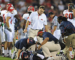 Ole Miss Head Coach Houston Nutt looks on as trainers attend to Ole Miss defensive end Kentrell Lockett (40) at Vaught-Hemingway Stadium in Oxford, Miss. on Saturday, September 25, 2010. Ole Miss won 55-38 over Fresno State. Lockett injured his ACL on the play and is out for the season.
