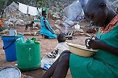 Liliosa (in blue), 16, cooks cornmeal in Masvingo Province, Zimbabwe, to feed herself, her baby and her young sister Letwin (in green), who is born HIV positive. <br /> <br /> Drought in southern Africa is devastating communities in Zimbabwe, leaving 4 million people urgently in need of food aid. The government declared a state of emergency,. <br /> <br /> Here in Masvingo Province, the country's hardest hit province, vegetation has wilted, livestock is dying, and people are at serious risk of famine. <br /> <br /> Pictures shot by Justin Jin