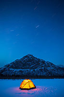 Yellow tent glows on the winter snow as stars trail across the sky over Mt Dillon of the Brooks Range mountains, Arctic, Alaska.