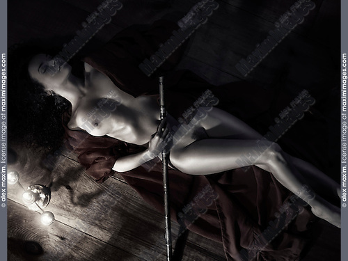 Beautiful nude woman with a bamboo flute in undone red kimono lying on the floor in dim dramatic candle light Black and white