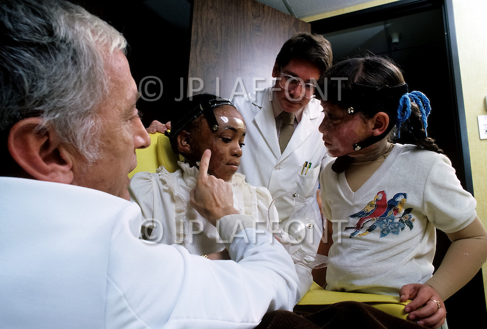 Los Angeles, U.S.A, January, 1983. The Sherman Oaks Hospital, a center  specializing in the treatment of seriously burned patients, is making remarkable progress: the team of Dr. Grossman has perfected several new inventions and some revolutionary treatments. Dr. Grossman explains to these  girls with facial burns how to wear their masks and the frequent modifications he will make during the period of healing. Dr. Feldman has created these new transparent masks.