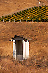 White wooden outhouse in a field near vineyards in the Santa Lucia Range near the Salinas Valley of Calif.