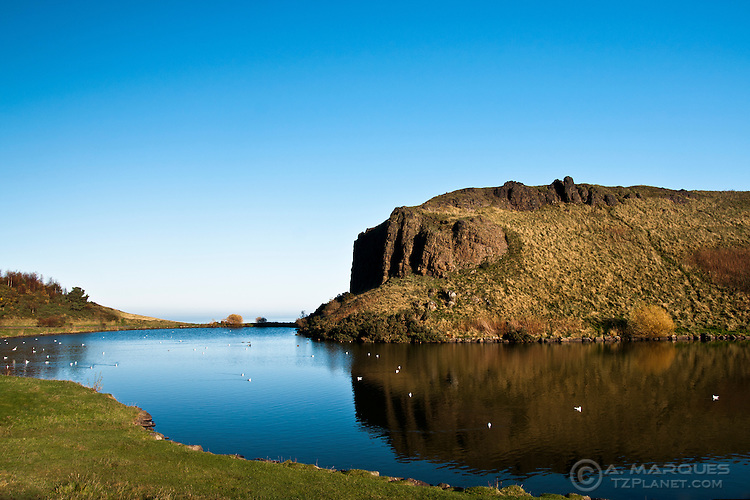 A cliff, Dunsapie Crag, reflected on the waters of Dunsapie Loch, Holyrood Park, Edinburgh, Scotland. The loch is located just to the East of the iconic Arthur's Seat.  .Dunsapie Loch is one of three lochs located within Holyrood Park (aka Queen's Park).  .Everytime I go for a walk around the area, I'm always amazed that such beautiful locations can still exist right in the middle of a capital city.